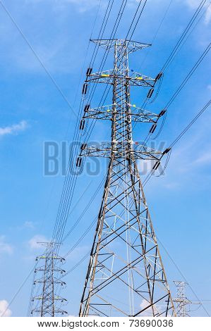 High Voltage Power Pole And Electricity Line With Blue Sky Background.