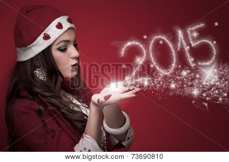 Beautiful young woman in the Santa costume blowing snowflakes and make New Year numbers 2015