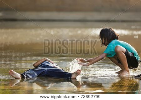 BANGKOK, THAILAND, DECEMBER 25, 2011: Little girl spreading some water on his brother lying in a puddle after the flood in Bangkok, Thailand
