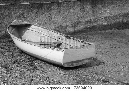 Weather-beaten Dinghy On A Concrete Slipway