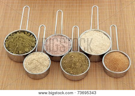 Protein and health supplement food powders in scoops. Hemp, ginseng, chocolate whey, ginkgo biloba, macca root and pomegranate left to right.
