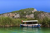 stock photo of dalyan  - River boat by the historic Kaunian rock tombs in Dalyan - JPG