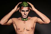 foto of beast-man  - fashion studio portrait of sexy muscular man with painted face and chest for Halloween party - JPG