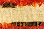 stock photo of happy thanksgiving  - Burlap background with wooden Happy Thanksgiving letterpress and autumn leaves - JPG