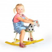 stock photo of horse girl  - Happy girl on a rocking horse - JPG