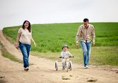 image of tricycle  - Happy family with little boy on wooden tricycle walking in ntaure - JPG