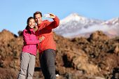 stock photo of canary  - Couple taking selfie hiking in beautiful nature with smart phone - JPG