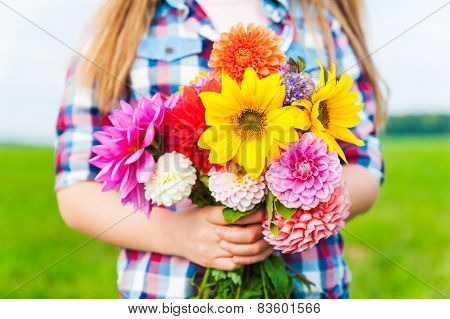 Beautiful bouquet of bright and colorful flowers holding by child's hands
