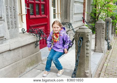 Adorable kid girl playing on a street, wearing purple rain coat, jeans and golden shoes