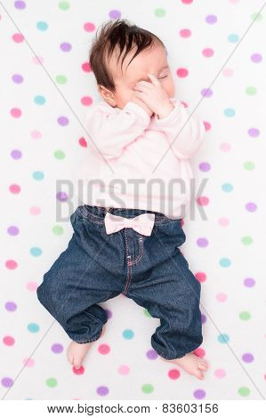 Little Baby Lying On Blanket With Colourful Polka Dots
