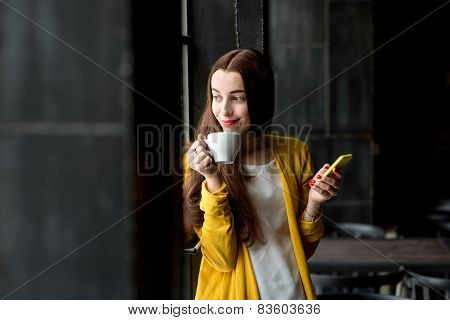 Woman with phone and a cup of coffee