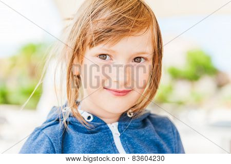 Outdoor portrait of a cute little girl with freckles