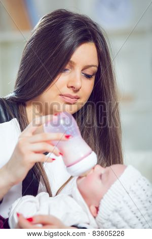 Young mother at home feeding their new baby girl with a milk bottle,