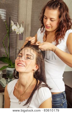 Beautiful Young Woman Makes The Hairstyle Of His Girlfriend At Home
