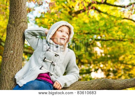 Autumn portrait of a cute little girl playing on a tree in a beautiful park on a nice sunny day