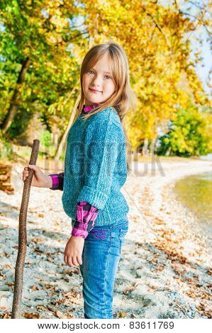 Autumn portrait of a cute little girl, playing by the lake, wearing blue pullover