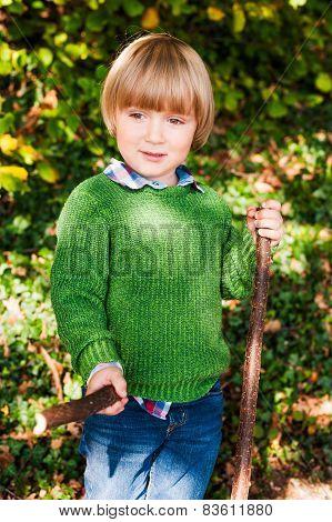 Outdoor portrait of a cute little boy, wearing green pullover