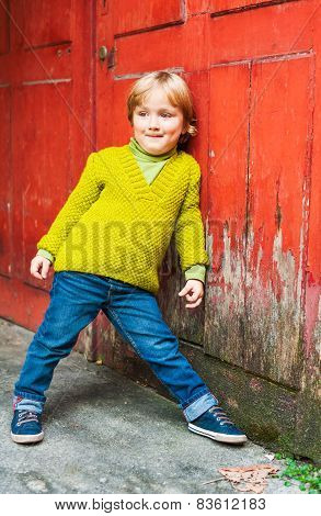 Outdoor portrait of adorable toddler boy, wearing bright green knit pullover, standing next to red d