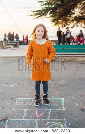 Cute little girl playing hopscotch on the street