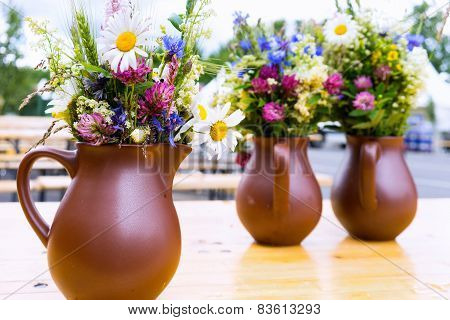 Pitchers With Bouquets Of Wild Flowers On The Table