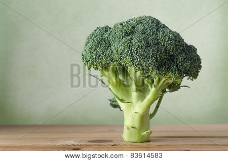 Broccoli Standing On Wood With Green Background