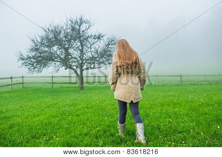 Outdoor portrait of a cute little girl in a garden on a foggy day, wearing warm beige coat