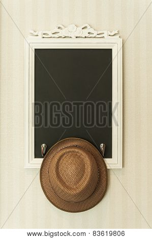 Vintage Slate Chalk Board With Brown Hat On The Wall