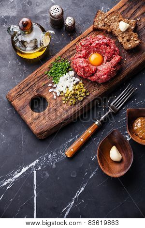 Beef Tartare With Pickled Cucumber And Fresh Onions On Dark Marble Background