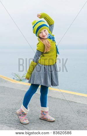 Cute little girl having fun outdoors on a cold day, dancing next to beautiful lake, wearing green wo