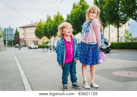 Adorable children playing on the street, kids in a city concept