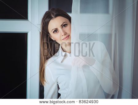 Woman peek out from the curtain