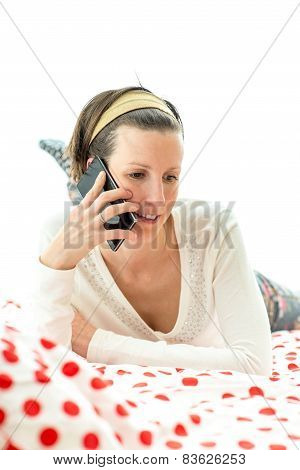 Young Woman Lying Chatting On A Mobile Phone