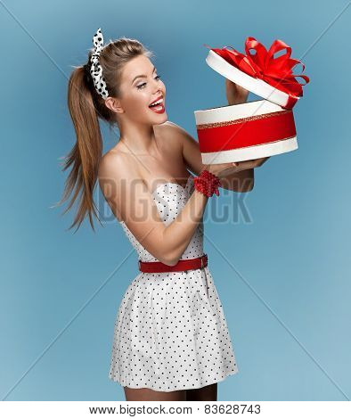 Surprised smiling beautiful young woman holding an open gift box and looking at the present. Holiday