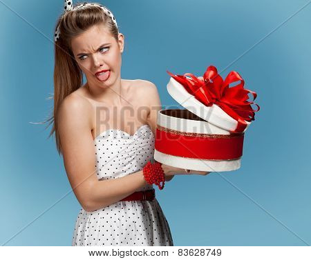 Girl is not satisfied with her gifts against blue background. Holidays, holiday, celebration, birthd