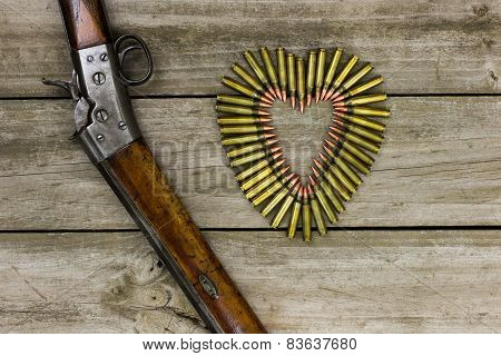 Rifle by heart-shaped bullets on wood background