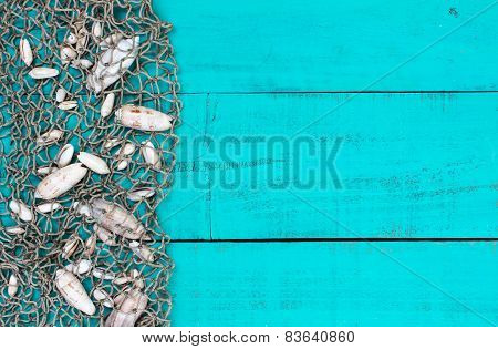 Shells in fish netting on teal blue wood sign