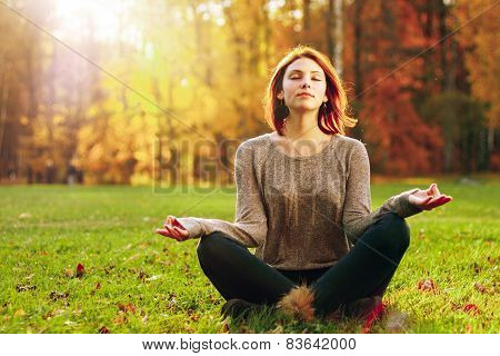 Young female meditate in park.