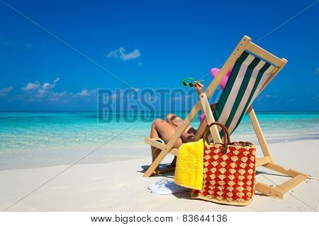 Young Girl Lying On A Beach Lounger With Sunglasses In Hand