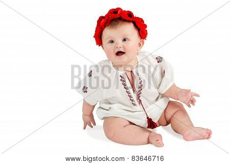 Cute baby with wreath of poppies sitting