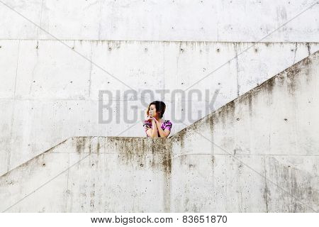 Young Attractive Asian American Woman By Cement Walls