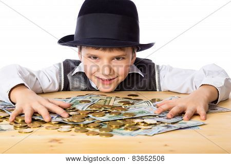 Happy boy with money on the table