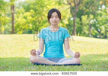 Asian Woman Practicing Yoga,breath Retention Pose, In Park