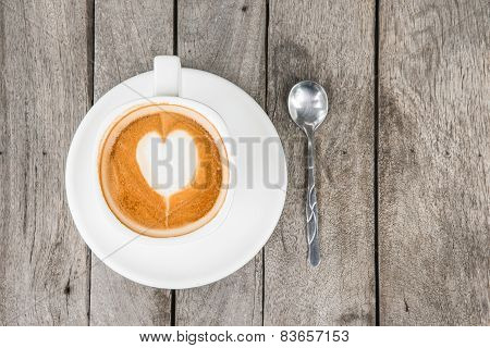 Coffee Cup With Heart Shape On Foam At Wood Table