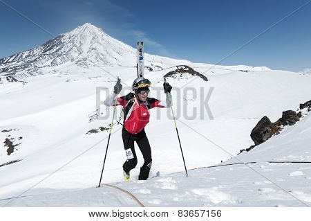 Ski Mountaineer Climb To Mountain With Skis Strapped To Backpack On Background Volcano