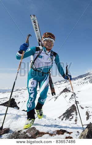 Happy Ski Mountaineer Climb To Mountain With Skis Strapped To Backpack