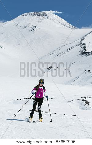 Ski mountaineering Championship: girl ski mountaineer rides skiing from volcano