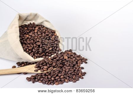 isolated bag with crumbled coffee beans and wooden spoon