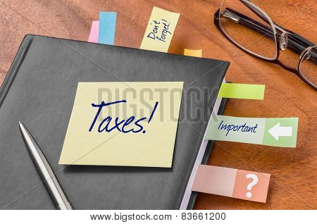 A planner with a sticky note - Taxes