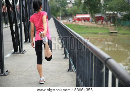 Runner athlete stretching on iron bridge. woman fitness jogging workout wellness concept.