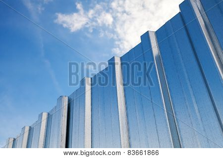 Shining Metal Fence And Blue Cloudy Sky